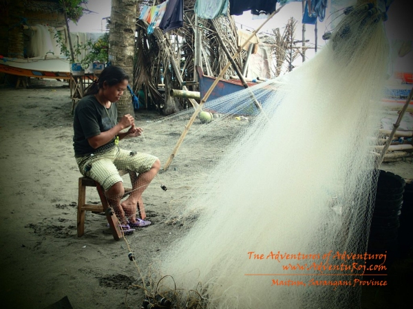 A local woman threading her net  in preparation for the catch